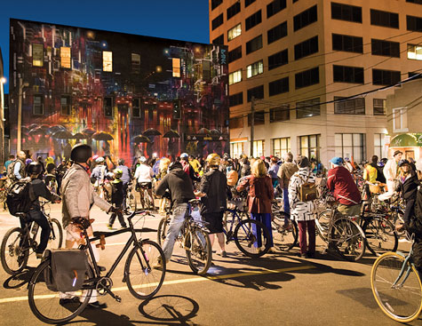 people outside on bikes stopped to view a painted mural during the disco bike ride during the annual art festival in moncton, new brunswick, canada