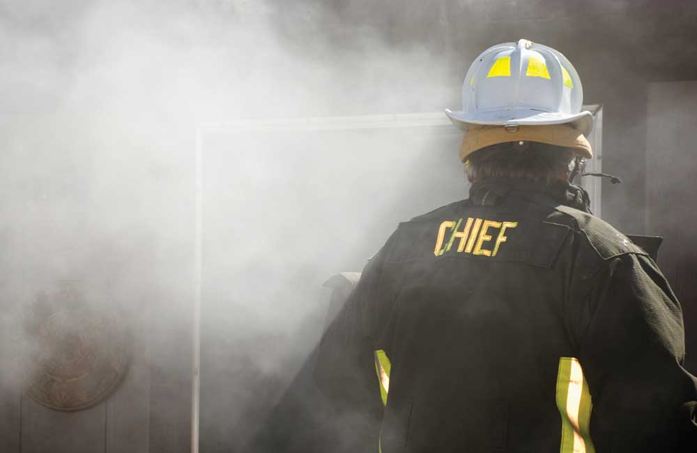 fire chief standing in front of smoke-filled dwelling