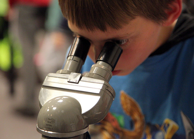image of child looking through a microscope