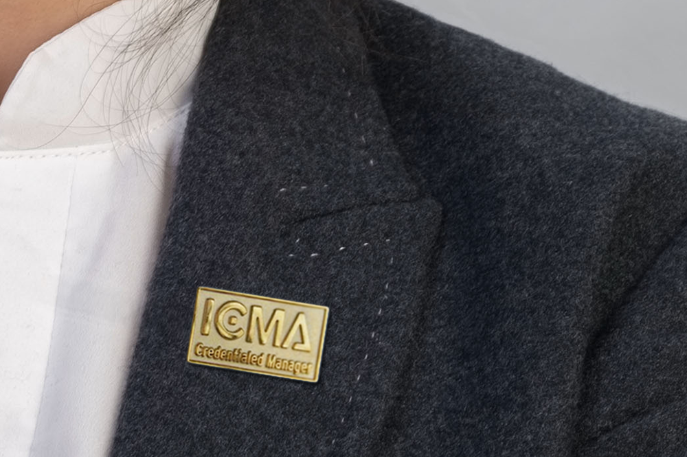 business woman in suit wearing credentialed manager pin