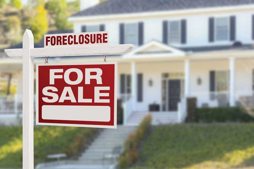 a for sale sign indicating a foreclosure in the yard of a large white house