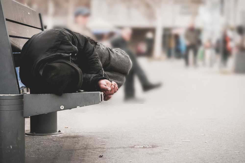 homeless person laying down on bench