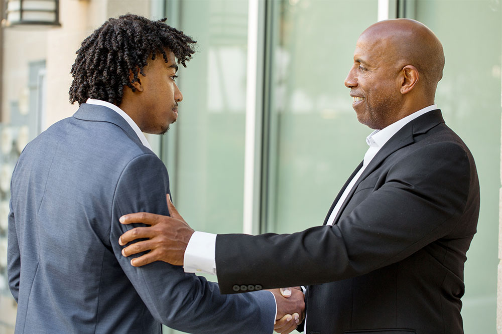 Mature African American  businessman shaking hands with younger business man