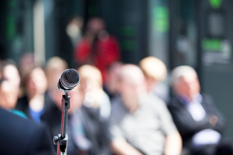 Photo of a microphone in front of an audience