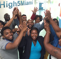 group of young black businessmen and businesswomen giving high fives in celebration