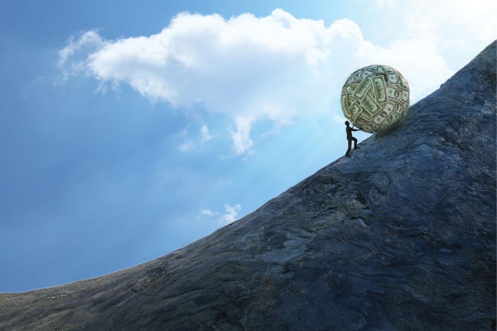 man rolling large ball of cash up hillside
