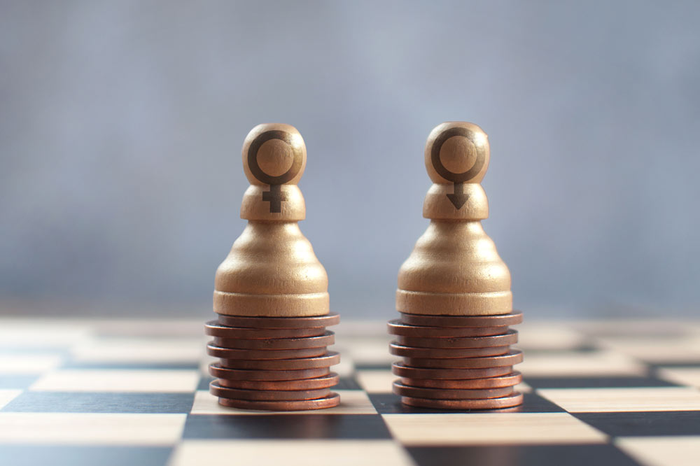 Equal gender pay, two chess pawns on top of two equal stacks of pennies