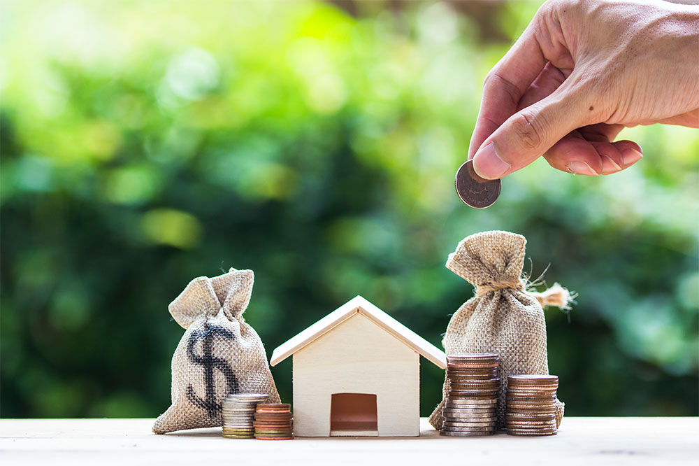 hand holding penny above house and money bags, investing in afforable housing