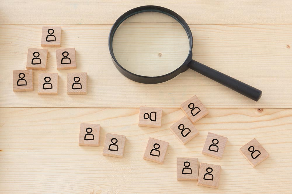 magnifying glass beside wooden scrabble pieces with the profile icon on them